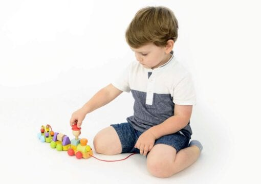 Young boy playing with a pull along train